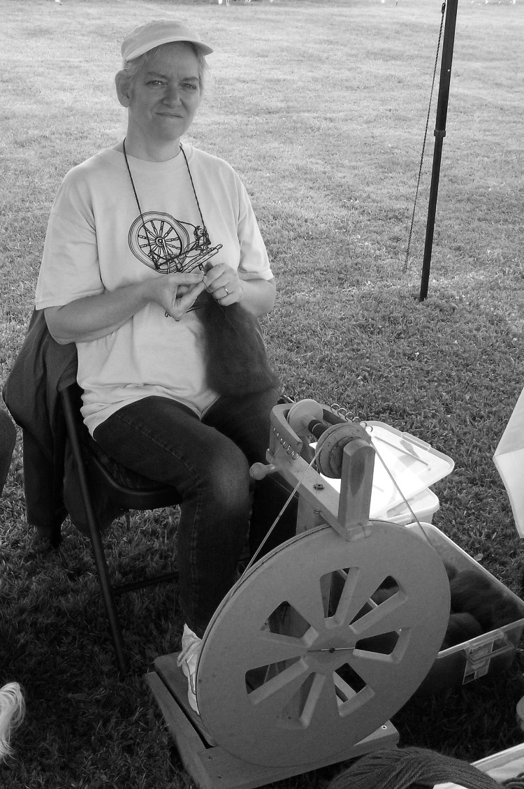 A lady spinning alpaca yarn using fiber from one of the local farms